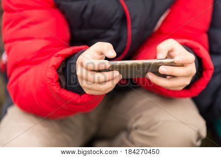 Boy playing computer games on a cell phone .