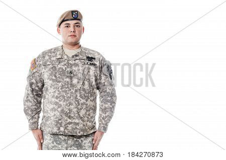Army Ranger from Special Troops Battalion in universal Camouflage pattern Uniforms and Tan beret with Ranger Regiment crest is standing to attention. National holidays Veterans Day, Memorial Day. National Anthem is played