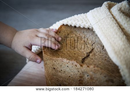 Home Made Cereal Bread In Yellow Cloth On Wooden Table With Child Hand