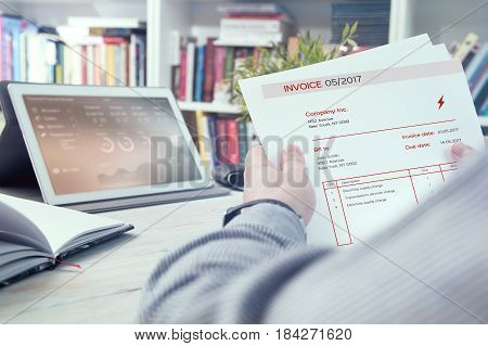 Man holds invoice of electric power usage