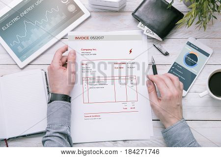 Man holds invoice of electric power usage over desk with tablet and smartphone with applications made in graphic program.