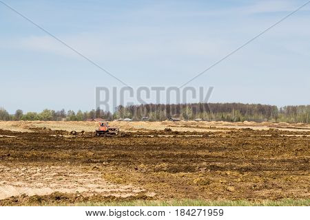 tractor preparing land with seedbed cultivator as part of pre seeding activities in early spring season of agricultural works at farmlands