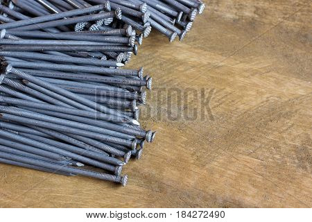 background of roofing nails on a wooden platform top view. empty space for Your text on the right.