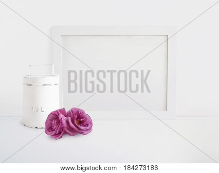 White blank wooden frame mockup with old tin and pink rose flowers lying on the table. Poster product design, styled stock feminine photography. Home decor.
