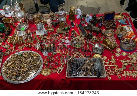 Moscow, Russia - March 19, 2017: Bronze, brass handmade souvenirs are spread out on the table mixed with antiques at a specialized fair for collectors