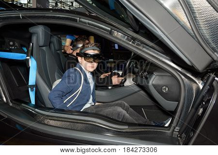 Boy tests the augmented reality in a BMW i8 using a HoloLens headset at the Intel booth at the CeBIT 2017. CeBIT is the world's largest trade fair for information technology.