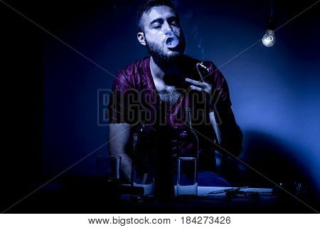 Young man with beard lost in the vices of alcoholism smoking and drug addiction