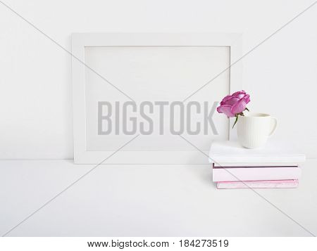 White blank wooden frame mockup with a rose flower in a porcelain cup and pile of books lying on the table. Poster product design, styled stock feminine photography. Home decor.