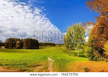 Autumn landscape view of golden autumn trees and colorful autumn valley in sunny day - autumn sunny view of the valley of Soroti river, Pushkinskiye Gory, Russia. Rural autumn landscape with forest autumn trees in the river valley -autumn background