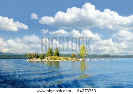 Summer water landscape of Gull Island on Turgoyak Lake, Southern Urals, Russia -soft focus applied. Picturesque summer landscape of mountain lake and stone island in summer sunny day. Sunny summer water landscape view. Summer background