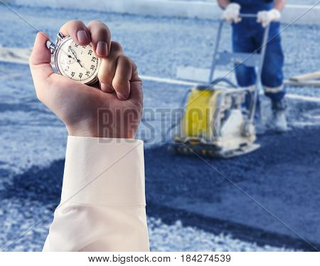 Worker Use Vibratory Plate Compactor And Stopwatch In Male Hand