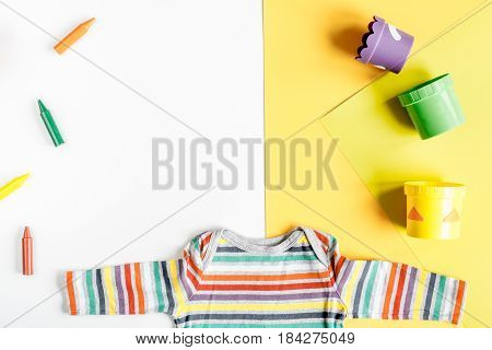 toys and clothes collection for child room on white and yellow table background top view mockup