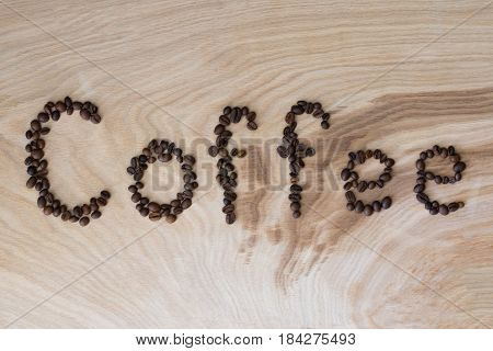 Word coffee laid out from grains on wooden background