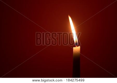 Holy religious white candle burning creating a mysterious atmosphere on a red background.