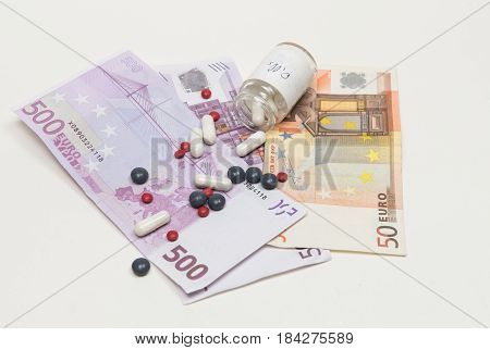 Euro banknotes and metical pills. Concept of expensive health care