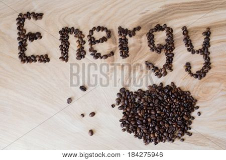 Word energy laid out from coffee grains on wooden background
