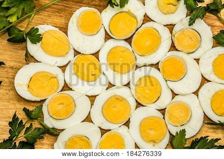 Boiled eggs cut in halfs decorated with fresh parsley leaves.