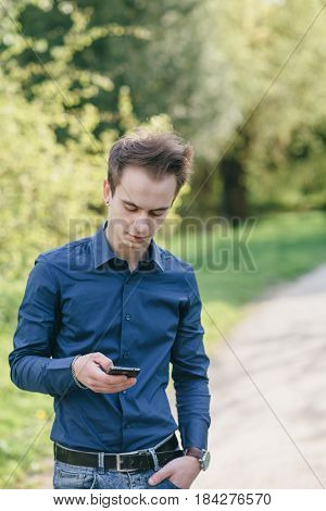 boy walks on spring park with phone, tablet and computer