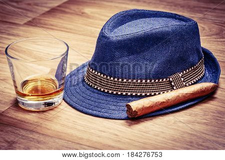 Blue Hat With Cigar And Expensive Drink Of Whisky Or Rum On Wooden Floor