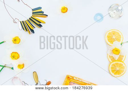 Top View White Background With Frame Of Fresh Daffodils, Botlle Of Perfume, Necklace And Lemon Slice