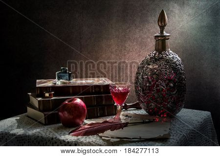 Set of vintage objects. Still life with  vintage wine decanter and  glass of wine, old books,  old  vintage paper,  feather and ink.