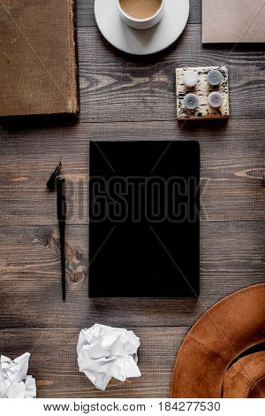 Writer workplace with tools, copybook and coffee on wooden table background top view