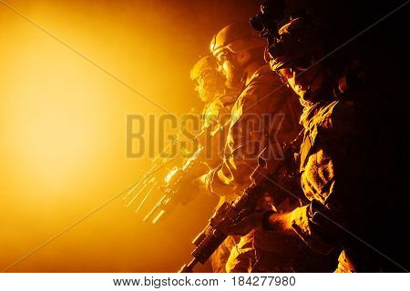 Group of security forces in Combat Uniforms with rifles, lined in the face of danger. Facing enemy, they stand boldly and ready to protect the nation. Studio contour silhouette shot, backlight, profile side view