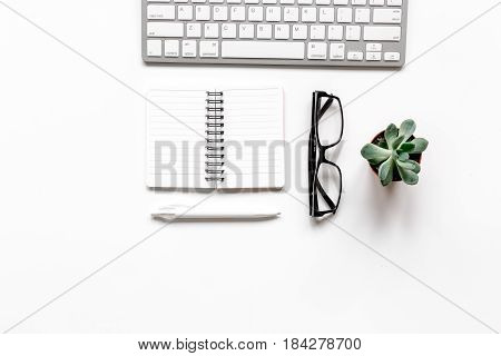 office desk design with notebook and glasses on white background top view space for text