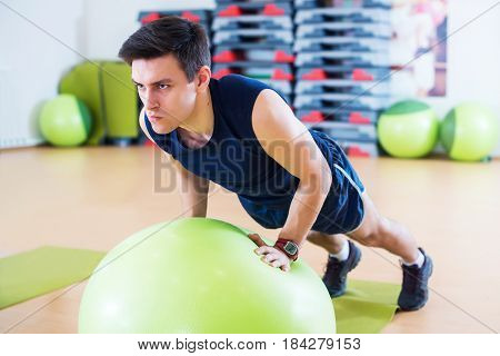 Fit man exercising with fit ball workout out arms Exercise training triceps and biceps doing push ups