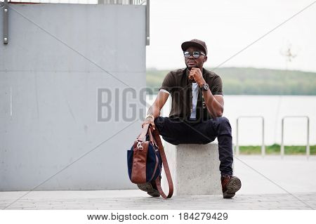 Portrait Of Sitting Stylish African American Man Wear On Sunglasses And Cap Outdoor. Street Fashion