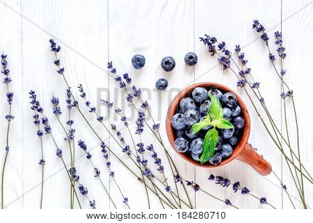 cup of blueberry and lavender flowers design on white wooden background top view space for text