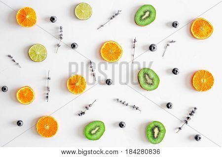 cut fruit design with blueberry and lavender on white wooden desk background top view pattern