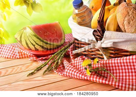 Picnic Wicker Basket With Food On Table In Field Elevated