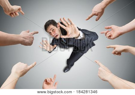 Many Hands Are Pointing And Blame Stressed Man. View From Top.