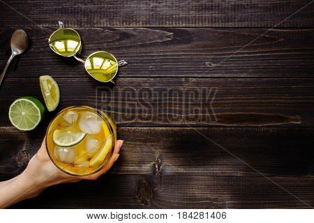 Hand Holding Ice Drink. Ice Tea, Lemon, Lime And Sunglasses On The Wooden Table, Top View. With Copy