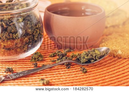 Dry leaves of green tea in a glass jar. Nearby tea leaves in a teaspoon and ceramic tea-things. Composition on a wattled napkin. The cover banks is open several tea leaves are scattered.