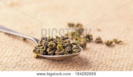 Dry leaves of green tea and teaspoon. A light background from sacking a close up selective focus. Grade milk oolong tea