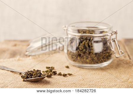 Dry leaves of green tea in a glass jar. Nearby tea leaves in a teaspoon. Composition on a napkin from a sacking. The cover banks is open several tea leaves are scattered. Light background