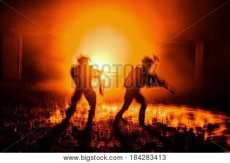 Dark silhouettes of pair of soldiers moving in battle operation. Back light
