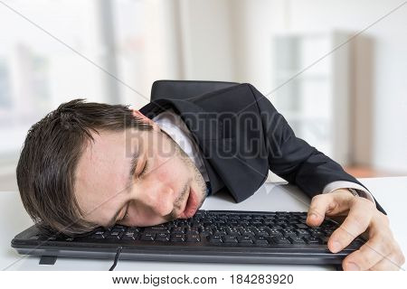 Exhausted Or Tired Businessman Is Sleeping On Keyboard In Office