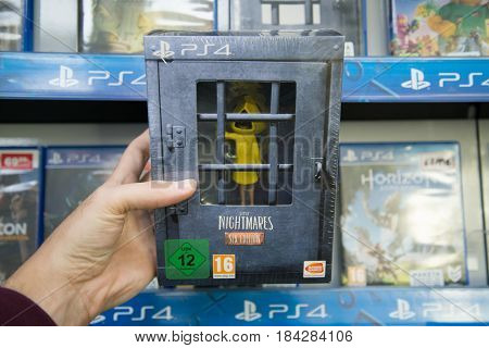 Bratislava, Slovakia, circa april 2017: Man holding Little nigtmares six edition videogame on Playstation 4 console in store
