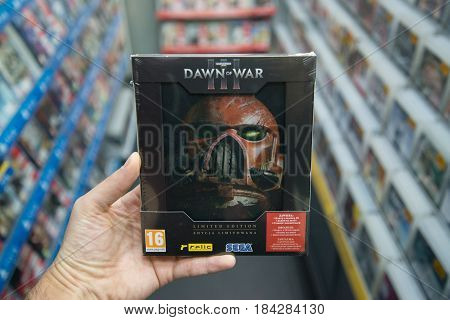 Bratislava, Slovakia, circa april 2017: Man holding Warhamer Dawn of War 3 limited edition videogame on PC in store