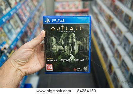 Bratislava, Slovakia, circa april 2017: Man holding Outlast Trinity videogame on Playstation 4 console in store