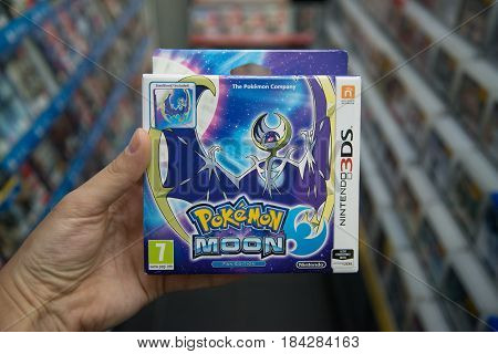 Bratislava, Slovakia, circa april 2017: Man holding Pokemon moon videogame on Nintendo 3DS console in store