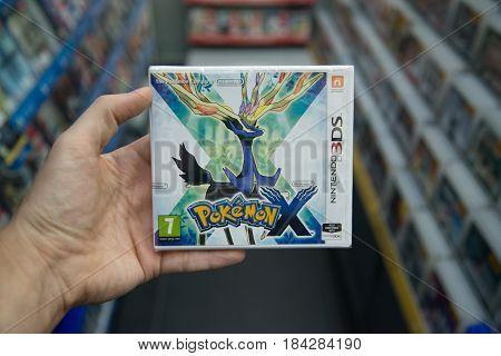 Bratislava, Slovakia, circa april 2017: Man holding Pokemon X videogame on Nintendo 3DS console in store