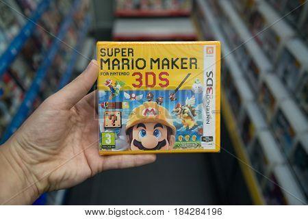 Bratislava, Slovakia, circa april 2017: Man holding Super Mario Maker videogame on Nintendo 3DS console in store