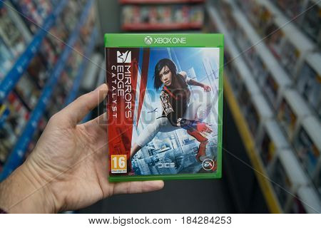 Bratislava, Slovakia, circa april 2017: Man holding Mirror's edge catalyst videogame on Microsoft XBOX One console in store