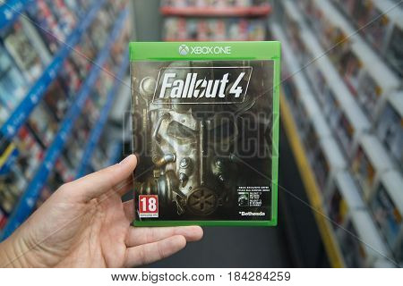 Bratislava, Slovakia, circa april 2017: Man holding Fallout 4 videogame on Microsoft XBOX One console in store