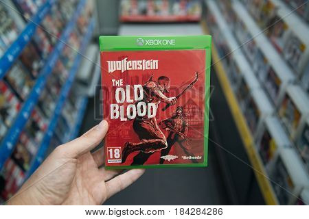 Bratislava, Slovakia, circa april 2017: Man holding Wolfenstein the Old blook videogame on Microsoft XBOX One console in store