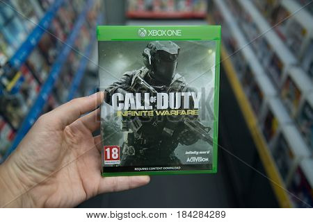 Bratislava, Slovakia, circa april 2017: Man holding Call of duty infinite warfare videogame on Microsoft XBOX One console in store